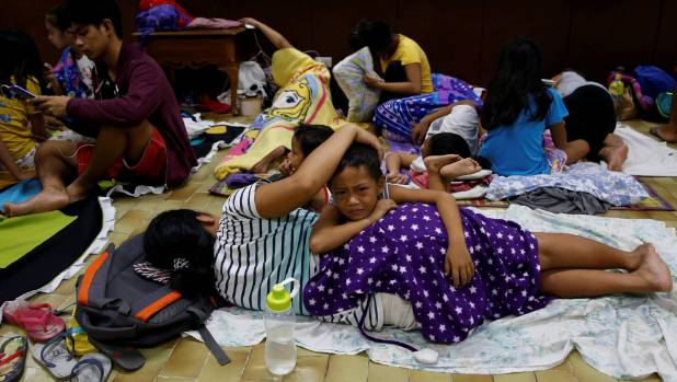 Residents who evacuated their homes due to Typhoon Haima take shelter at an evacuation centre in San Fernando, la Union ...