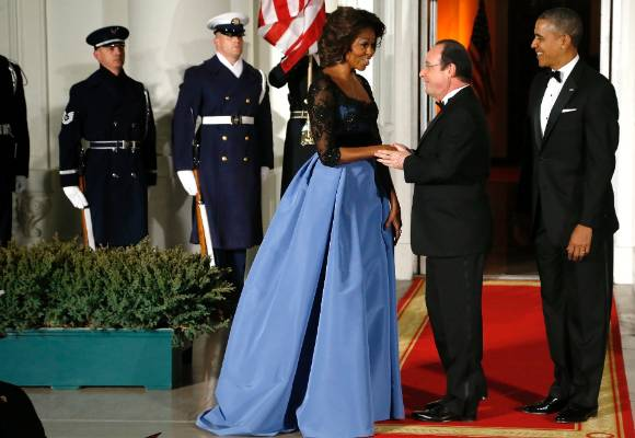 This is serious drama from Carolina Herrera. Michelle is shaking hands with French President Francois Hollande and ...