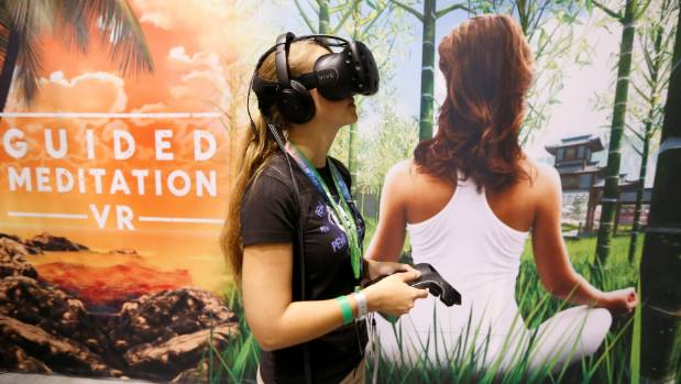 A woman is using a virtual reality headset to play a guided meditation video game in California. Virtual reality will be ...