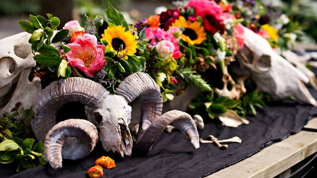 Found bones and skulls incorporated with soft florals make a sophisticated Halloween table setting.