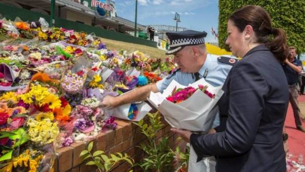 Queensland Premier Annastacia Palaszczuk and Assistant Commissioner Brian Codd pay their respects at Dreamworld.