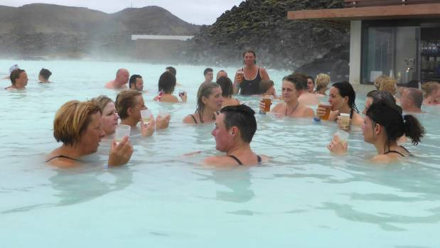Visitors enjoy a drink in the Blue Lagoon geothermal spa in Grindavik, Iceland.
