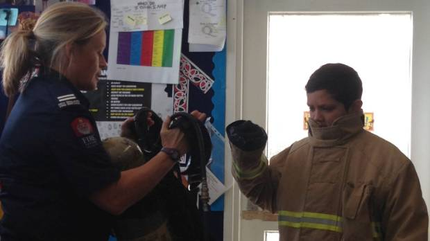 Belinda Cadzow from the New Zealand Fire Service, shows Riverdale School pupil Jimi Gray how to dress as a firefighter.