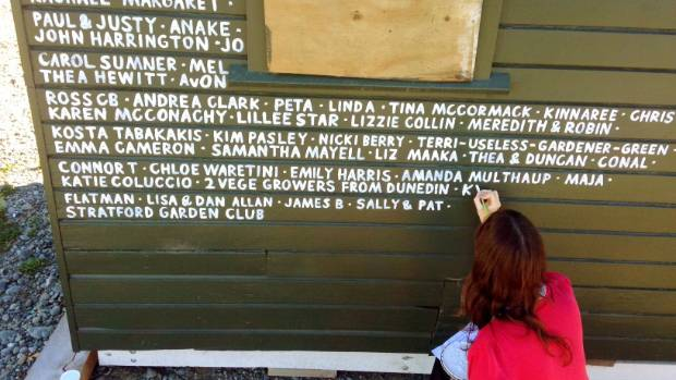 Chloe Waretini, of the Food Resilience Network, paints the names of donors to the Okataro Orchard on a shed on the site.