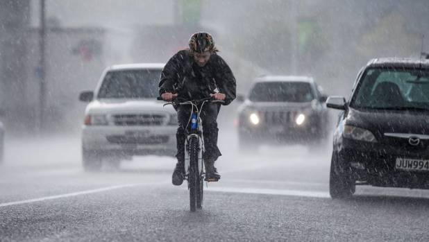 A cyclist battles hail and heavy rain on Colombo St on Thursday afternoon.