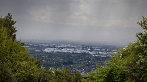 Bands of heavy rain sweep across Christchurch in this view from Victoria Park on the Port Hills.