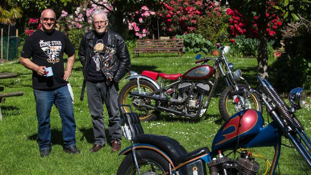 Paddy, on the left and Dr Kerry Swanson, aka Swannie, stand in a garden area with a couple of motorbikes, Paddy has a ...