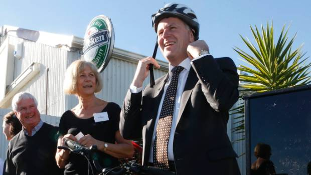 Former Prime Minister John Key straps up his bicycle helmet. Police said monitoring helmet use was not a priority.
