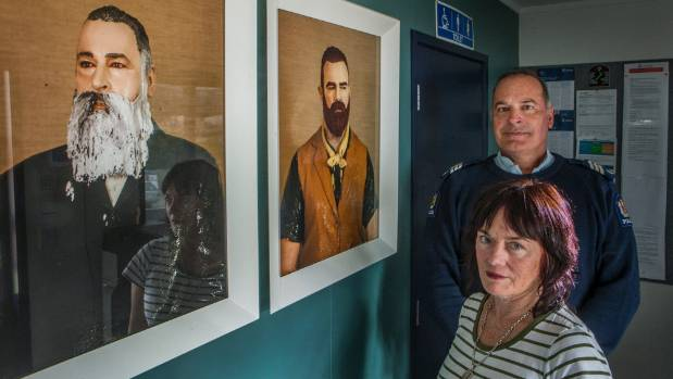 Artist Julia Holden and Sergeant Dave Knowles stand in the Lyttelton Police Station alongside images of Henry J Tancred ...