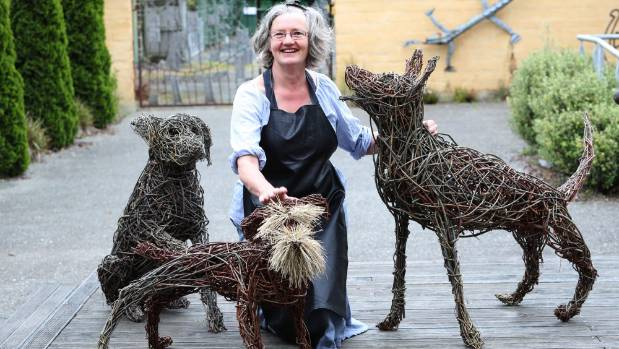 Deborah Walsh with woven willow quirky dogs in the garden area outside the Refinery ArtSpace.