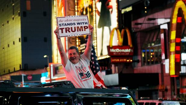 A jubilant Trump supporter drives through Times Square in New York.