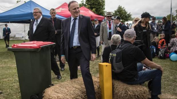 Prime Minister John Key straddles a hay bale.