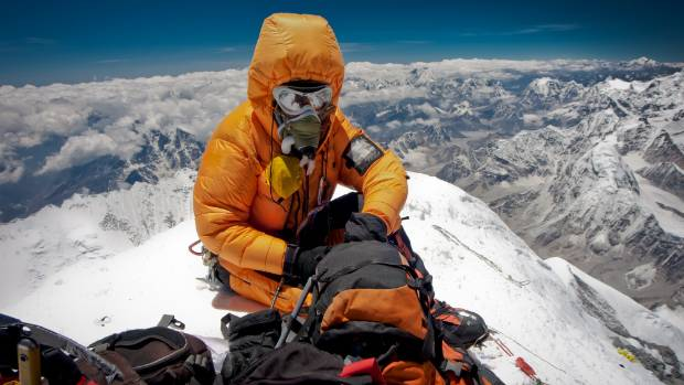 A climber resting, alone on the summit of Mount Everest, the highest mountain in the world.