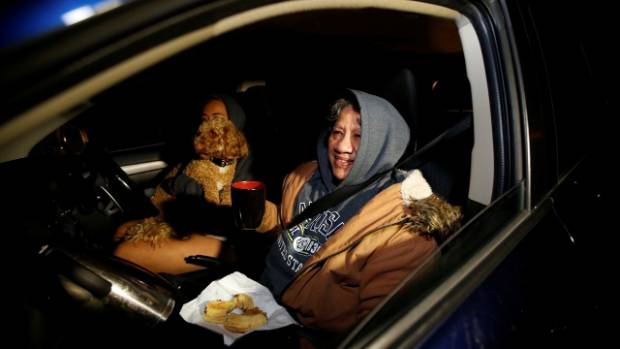 Rachel Tevita (obscured by dog Max) with mother Lucy Tevita (right) with other family members, holed up in car amongst ...