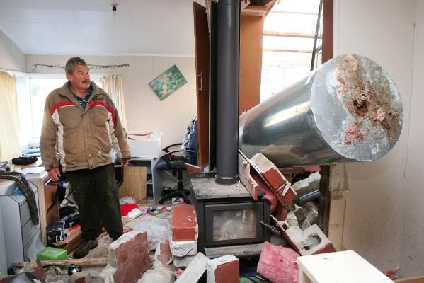 Ward resident Bryan Phipps surveys the damage to his Ward home after this mornings earthquake.