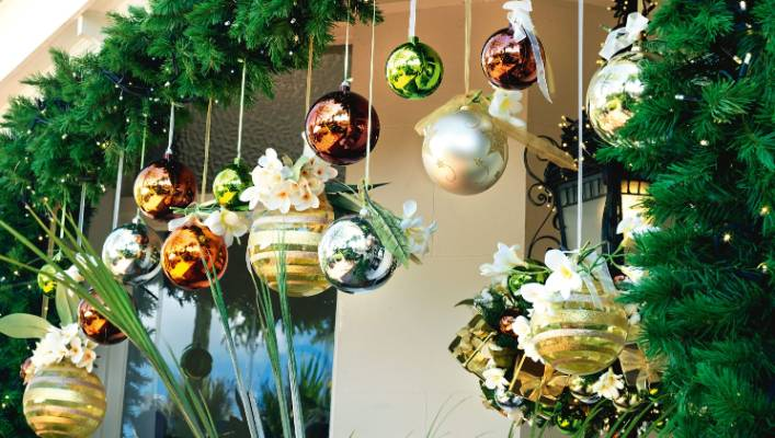 tropical flowers such as frangipani add a touch of summer to traditional christmas decorations
