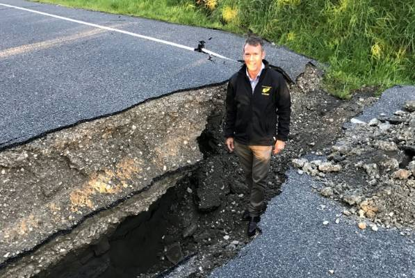 Stuart Smith stands in a crack in the road at Tirohunga flat near Kaikoura.