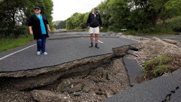 Local residents Chris and Viv Young look at damage along State Highway 1 near the town of Ward.
