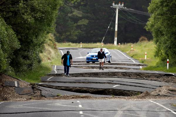 Local residents Chris and Viv Young look at damage caused by an earthquake along State Highway 1 near the town of Ward.
