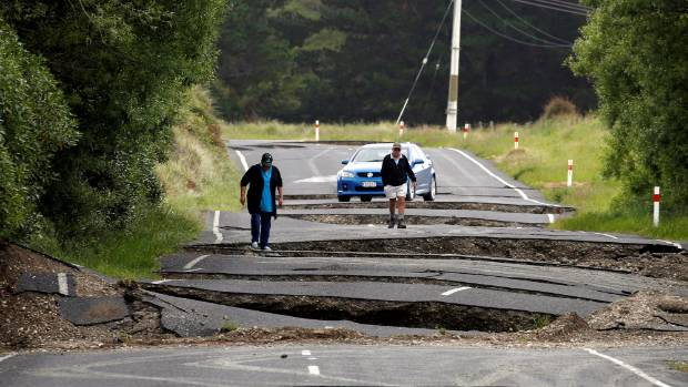 Residents Chris and Viv Young look at damage caused by an earthquake along State Highway One near the town of Ward, ...