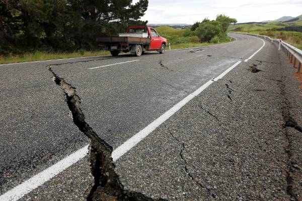 A truck drives over fractures caused by the earthquake, along a road south of Ward.