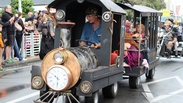 A steampunk train carries passengers in its carriage at the 2016 Steampunk the Thames parade.