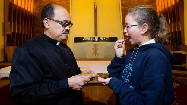 St Joseph's Parish Waitara's Father Freddie Barte provides Amene-ia Jury with a gluten-free communion wafer.