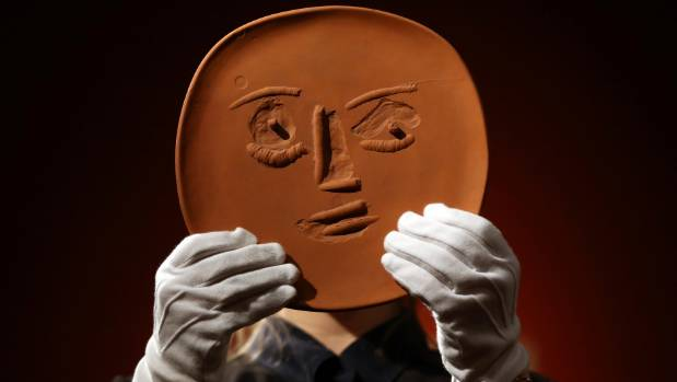 An unglazed terracotta plate entitled 'Visage aux grands yeux' by Pablo Picasso.