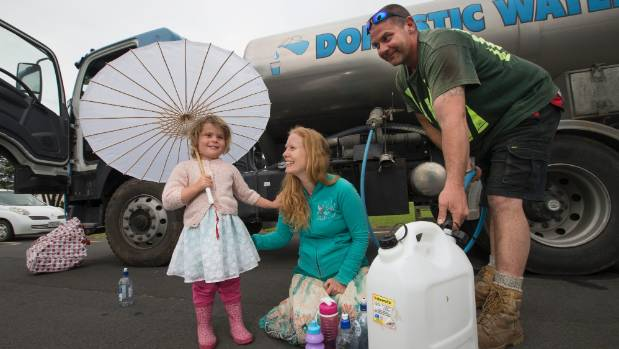 Luke Firmin fills Melissa Delaux and her daughter Neave Delaux, 3, drinking water containers after earthquakes caused ...