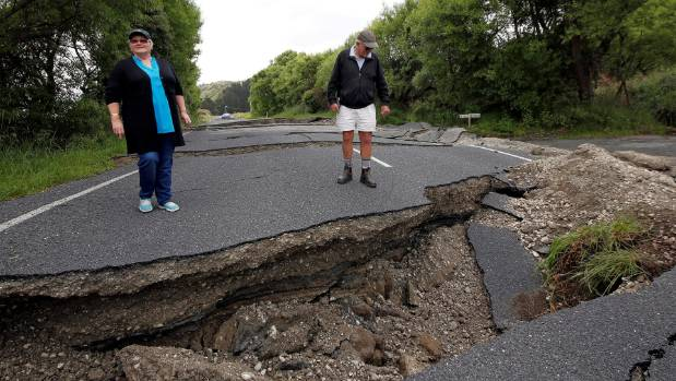Chris and Viv Young look at damage caused by an earthquake along State Highway One near the town of Ward, south of Blenheim.