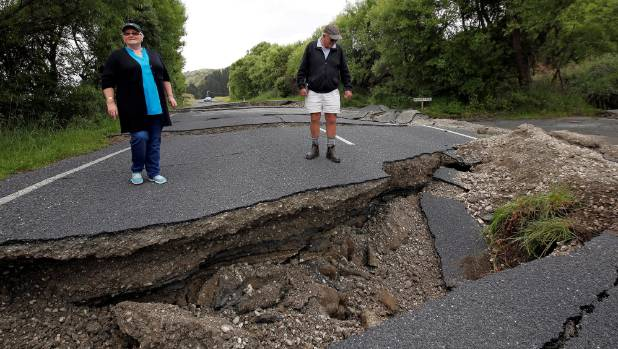 Ward residents Chris and Viv Young look at quake damage on State Highway 1.