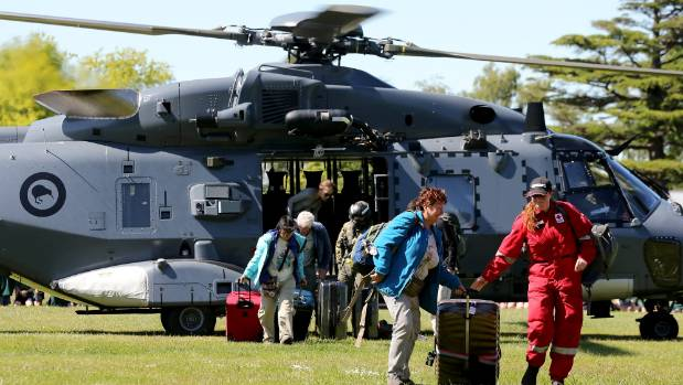 Tourists trapped by the Kaikoura earthquakes arrive by military helicopters at Woodend School grounds in Christchurch.