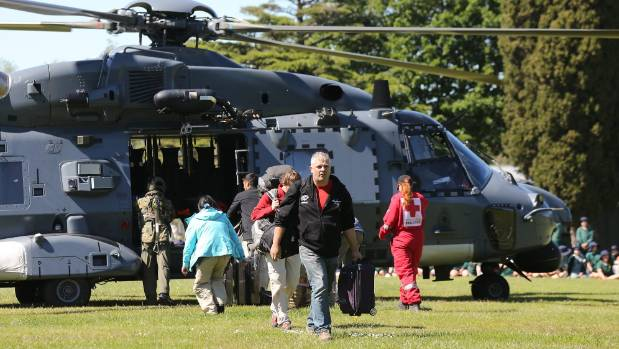 Tourists trapped by the Kaikoura earthquake arrive by military helicopters at Woodend School grounds in Christchurch.