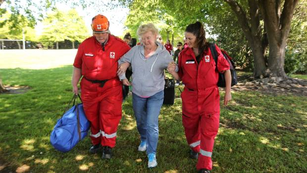 Medical staff assist a Kaikoura quake evacuee from a military helicopter.