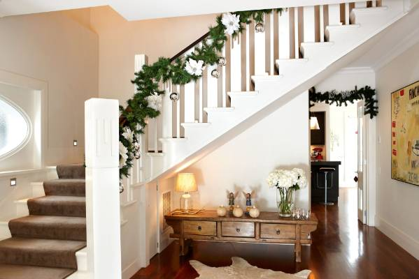 Christmas greenery or tinsel wrapped around the balustrade is a classic yet simple decoration for any two storey home.