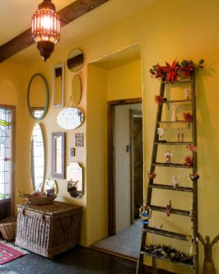 Decorating a ladder with ornaments and mistletoe is a creative replacement for a Christmas tree in a minimalist home.
