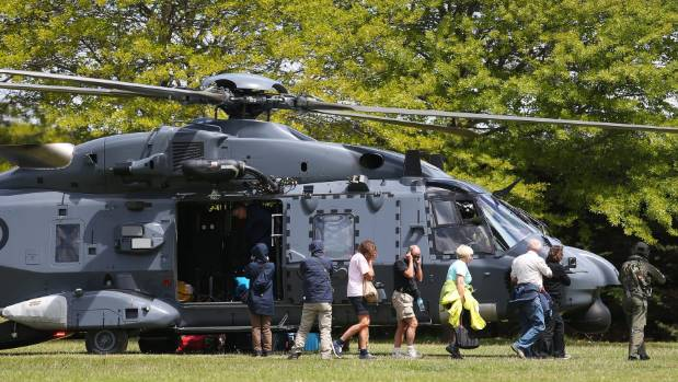 Tourists disembark a military helicopter transporting earthquake evacuees from Kaikoura, landing in the Woodend School ...