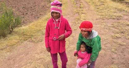 Young children, dressed in bright, bold colours, play on the outskirts of the village of Chinchero in Peru's Maras plateau.