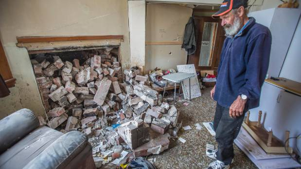 Clive Murdoch asseses the damage after the chimney collapsed in his bedroom in his Waiau home.