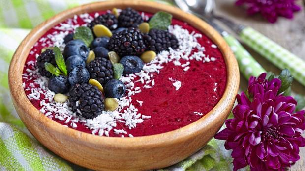 An Acai bowl with blackberry, blueberry, coconut and pumpkin seeds.
