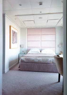 Sky high: This pink upholstered headboard makes it all the way to the ceiling in this luxury apartment.