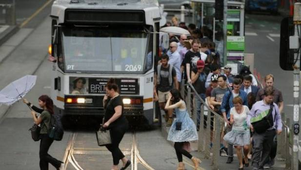 Commuters get off a tram in wild weather in Melbourne on Monday.