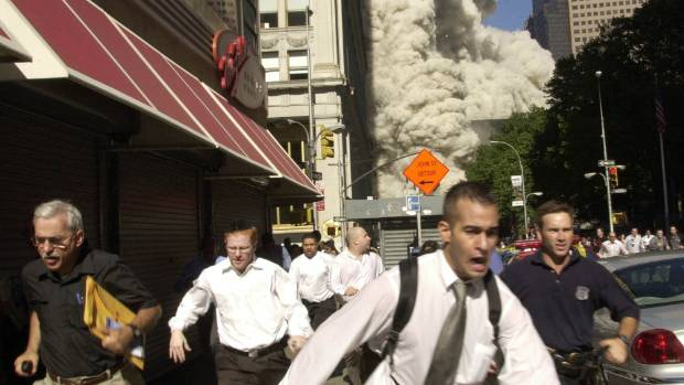 People flee as the World Trade Center Tower collapses behind them in 2001.