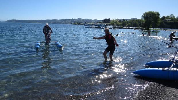 Andrew Elliston waves Mike O'Sullivan as the pair complete their cycle journey across Lake Taupo from Tokaanu to Taupo ...