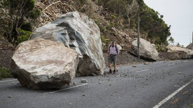Numerous boulders as well as slips block lanes on the highway.
