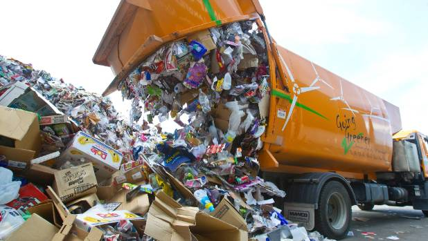 A recycling truck unloads its material.