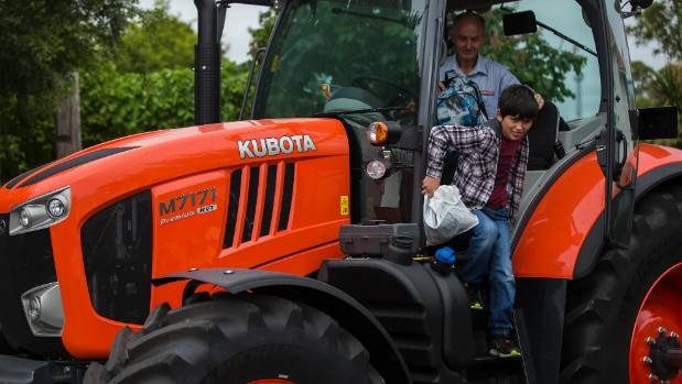 Miko Owen, 11, climbs down from a Kubuto tractor.