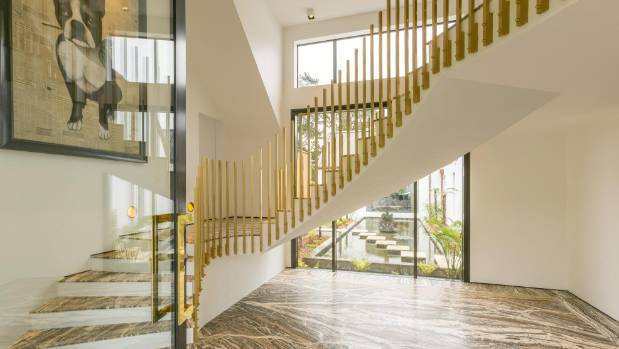 A travertine floor and winding staircase with gold balustrades create an appropriate grand entry for the house.