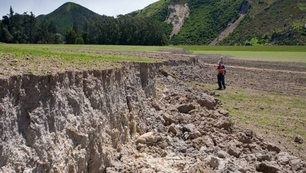 "Researcher Duncan Noble stands next to a ""very large left lateral fault scarp (steep slope caused by an earthquake) on ..."