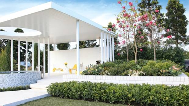 A white, freestanding block wall provides an excellent windbreak and a vertical surface for outdoor art.